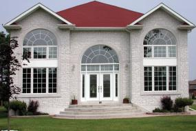 Shouldice Designer Stone - Grey house with front door and windows with Roman surrounds
